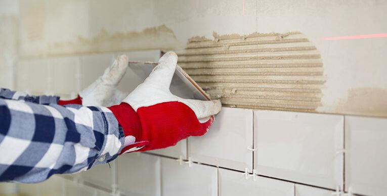 Pose de carrelage au mur dans une cuisine. Comme une crédence, le carrelage protège le mur.